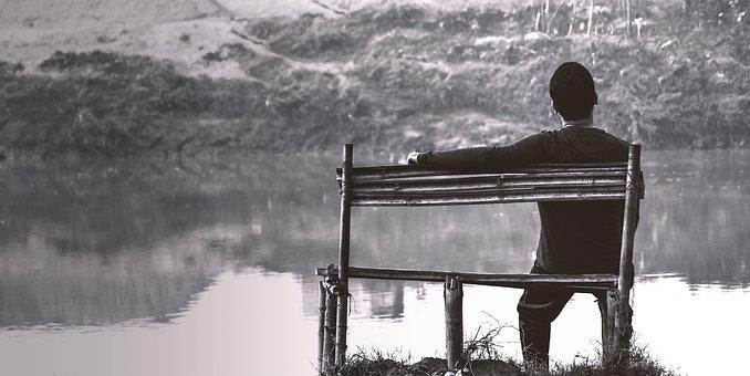 湖畔のベンチに腰掛ける1人の男性