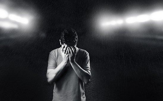 顔を覆って悲しむ男性
