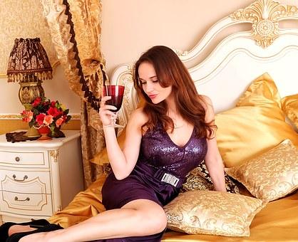 ベッドでワインを飲む女性