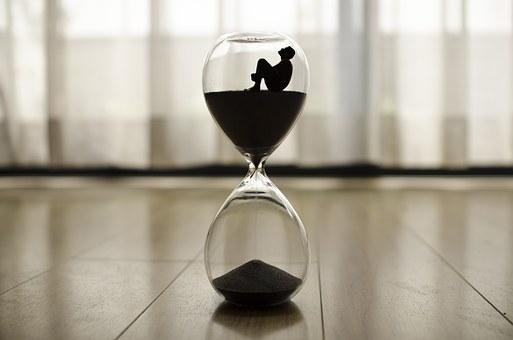 砂時計と男性のシルエット