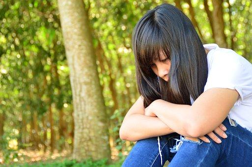 膝を抱えて悲しそうな女性