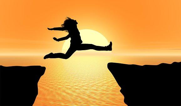 崖を飛び越える女性のシルエット