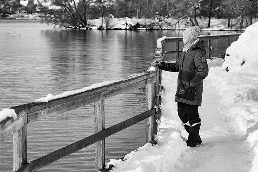 冬の湖の畔に立つ女性