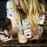 コーヒーを飲みながらスマホを操作する女性