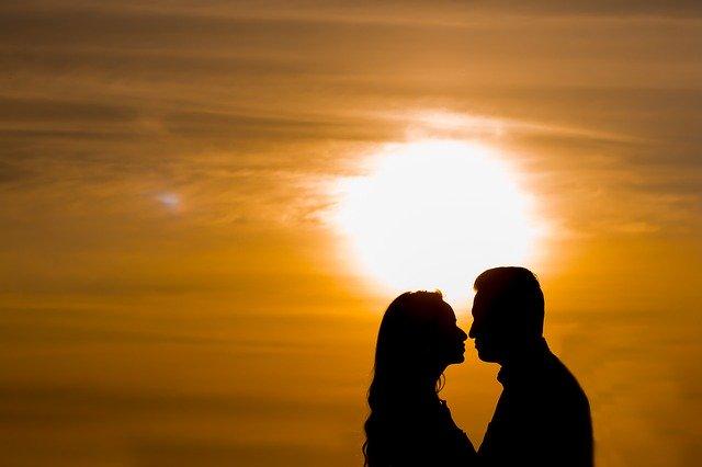 夕焼けと向き合うカップルのシルエット