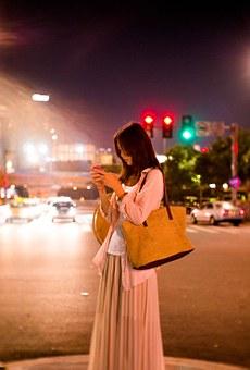 夜の街でスマホを操作する女性