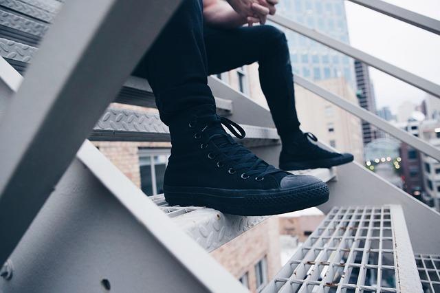 階段に腰掛ける男性の足下